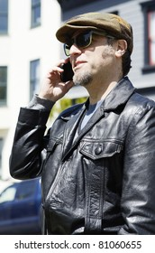 A man wearing a cap and sunglasses using his cellphone in the street