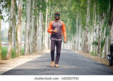Man wearing cap and sunglasses walking in an empty street