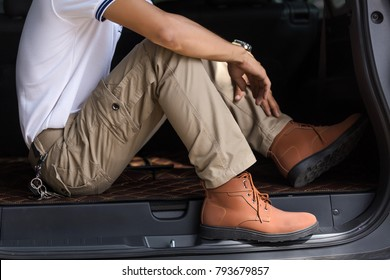 Man wearing cargo pants sitting in suv car parking in the nature park