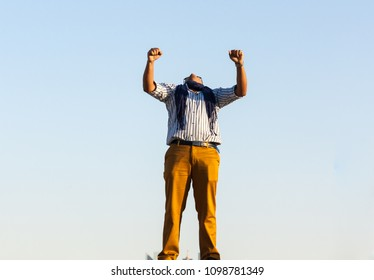 Man wearing casual dress with shawl around his neck showing hurray sign with both his hands outside shoot from lower angle with plan light blue sky as background