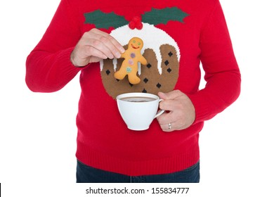 Man wearing a Christmas jumper about to dip a gingerbread man in a cup of hot chocolate, isolated against a white background.