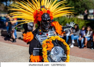 Man wearing colorful skull mask and paper flowers for Dia de Los Muertos/Day of the Dead