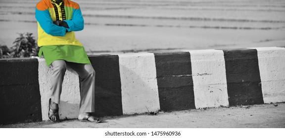 Man wearing colourful punjabi dress sitting around a place
