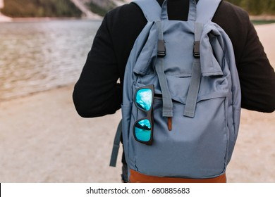 Man wearing cotton black sweater standing in front of lake with stylish travel bag and sunglasses. Outdoor portrait of guy carrying big blue backpack walking near river with rucksack on foreground.