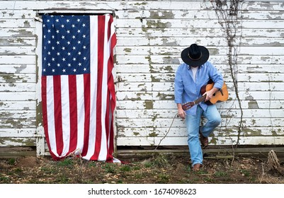 man wearing cowboy hat, old abandoned barn in the country holding acoustic guitar, color photo, american flag hanging, barn door, freedom, country, usa, independence, playing, singing, portrait, music