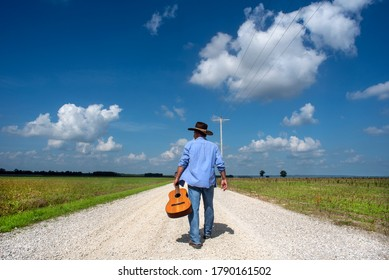Man wearing cowboy hat walking down one lane dirt gravel country road alone, acoustic guitar, blue sky, white clouds, independent, traveling, music, rural country, back to camera, portrait