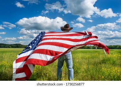 Man wearing cowboy hat waving American flag standing in grass farm agricultural field blue sky white clouds,  holidays, patriotism, pride, freedom, conservative, political parties, immigrant, voters