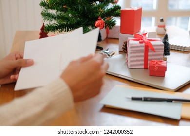 man wearing cream sweater opening sending christmas letter greeting card holiday wishes with xmas decoration