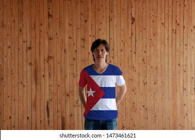 Man wearing Cuba flag color of shirt and standing with crossed behind the back hands on the wooden wall background, blue and white with the red equilateral triangle and star.