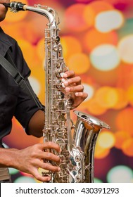 Man wearing dark shirt playing saxophone, blurry lights background and seen from profile angle
