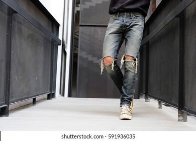 A man wearing denim destroyed jeans  in street look are walking