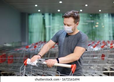 Der Mensch mit einer Einweg-medizinischen Gesichtsmaske wischt den Warenkorb mit einem Desinfektionstuch im Supermarkt ab. Sicherheit während des Ausbruchs von Coronavirus. Epidemie des Virus covid.