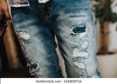 The man wearing distressed jeans. Fashion blue denim jeans. Closeup at ripped on jeans.