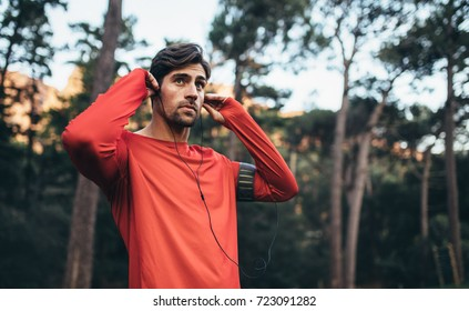 Man wearing earphones looking away. Runner listening to music during morning jog.