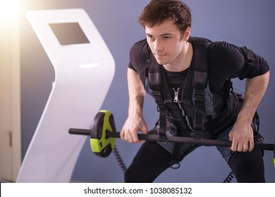 Man wearing EMS costume working out with barbell closeup, power pose