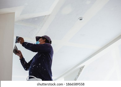 A man wearing a face mask applies putty to a ceiling of an almost complete home. Wearing clothes full of paint splotches.