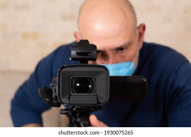 Man wearing face mask, looking to view finder of the camera and filming.