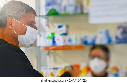 Man wearing face mask in the pharmacy. Coronavirus emergency. Paying by credit card.