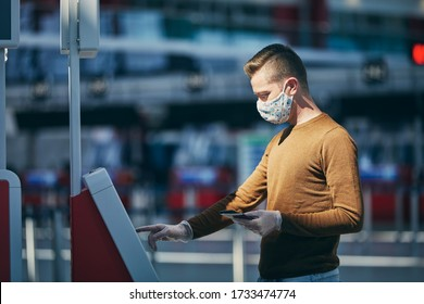 Man wearing face mask and using check in machine at airport. Themes traveling during pandemic and personal protection.