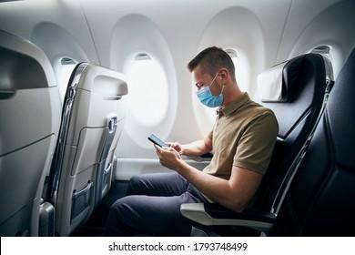 Mann mit Gesichtsmaske und mit einem Handy im Flugzeug während des Fluges. Thematisiert neue Normalität, Coronavirus und persönlichen Schutz.