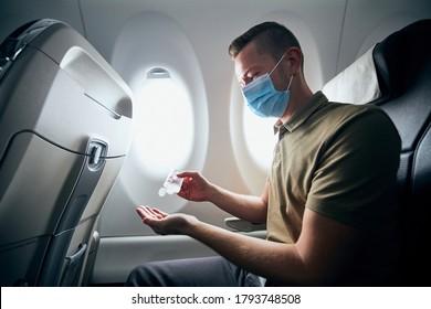 Man trägt Gesichtsmaske und benutzt während des Fluges Handanitisierer im Flugzeug. Thematisiert neue Normalität, Coronavirus und persönlichen Schutz.
