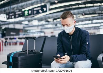 Mann mit Gesichtsmaske und wartet auf den Flug am Flughafen. Themen, die während der Pandemie und beim persönlichen Schutz reisen.