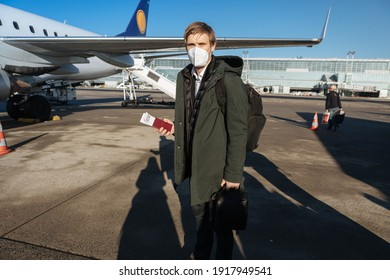 A man wearing face mask while standing next to airplane with passport. New normal traveling during a pandemic. Male passenger traveling by plane. Wearing mask in aircraft cabin. Air travel Covid 19