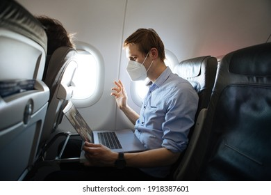 A man wearing face mask while sitting into an airplane. New normal traveling during a pandemic. Male passenger traveling. Wearing FFP2 mask in aircraft cabin. Travel Covid-19 Work from plane on laptop