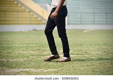 Man wearing a fashionable jeans pants & leather shoes walking on a field stock photo