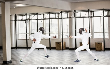Man wearing fencing suit practicing with sword against interior view of a gym