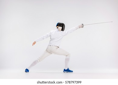 Man wearing fencing suit practicing with sword against gray studio background