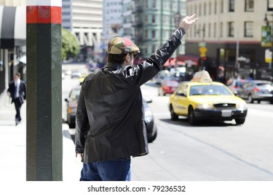 A man wearing a funky cap and black leather jacket at the side of the street hailing a taxi cab