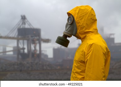 Man wearing gas mask standing infront of factory. Side shot. Background out of focus