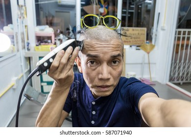 Man wearing glasses cutting his hair with clippers machine.
