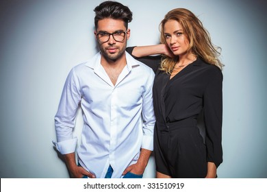 man wearing glasses pose with hands in pockets while woman rests her arm on his shoulder