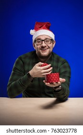 A man wearing glasses and wearing a Santa Claus hat holds gifts in his hands, posing on a blue background