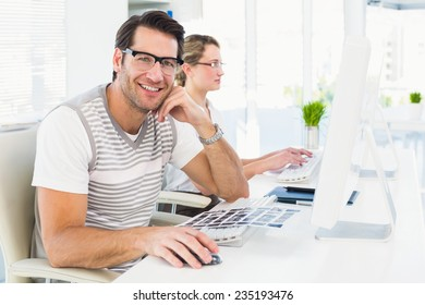 Man wearing glasses sitting at desk looking at camera in his office