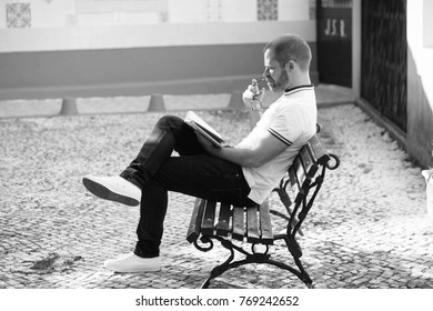 A man wearing glasses is sitting on a bench and reading a book. With shallow depth of field.
