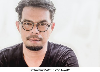 A man wearing glasses, wear black shirt, a mustache and beard, sitting in front of the house, casting stress on white background , soft focus , blurred.