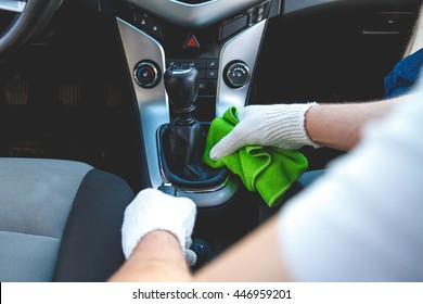 Man wearing gloves to clean the dashboard of the car. Auto Service