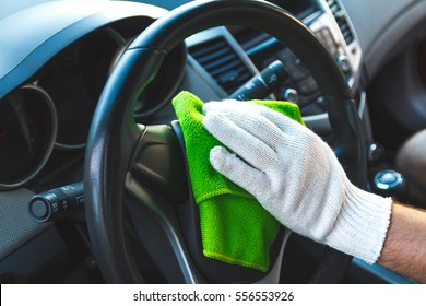 Man wearing gloves to clean the dashboard of the car. Auto Service.