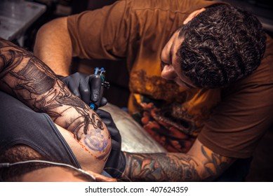 Man wearing gloves making a tattoo in tattoo parlor