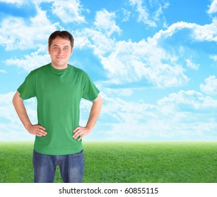 A man wearing a green t-shirt is smiling and standing in front of bright blue clouds and green nature grass. Use it for a recycling, peace or happiness concept.