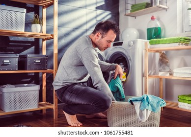 Man wearing grey sweater putting clothes into washing machine at laundry room