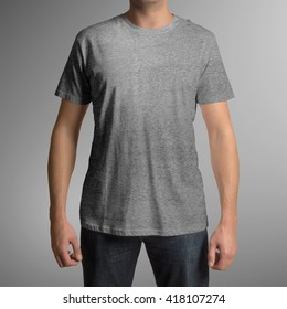 Man wearing grey t-shirt isolated on gray background, with clipping path to change background