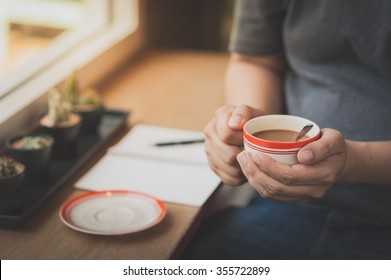 The man wearing grey t-shirt sitting beside window in cafe holding coffee cup in his hand in afternoon time with vintage filter effect