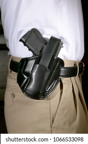 Man wearing a handgun in a black leather holster attached to his belt in a close up side view