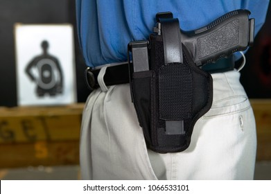 Man wearing a handgun in a webbing holster with strap attached to the belt in his pants in a close up side view at a target range