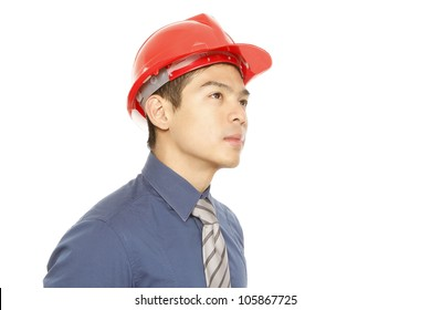 A man wearing a hard hat dreaming or thinking