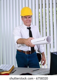 A man wearing a hardhat giving what appears to be drawings to someone